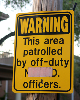 A sign announcing the presence of off-duty NOPD patrols in the Uptown area. (UptownMessenger.com file photo by Sabree Hill)