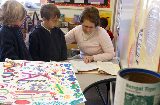 Teacher Elena Countiss helps Austyn Millet, 8, and  Aidan  Sierra, 8,  in a 2nd grade Spanish immersion classroom at the The International School of Louisiana Wednesday afternoon. (Sabree Hill, UptownMessenger.com)