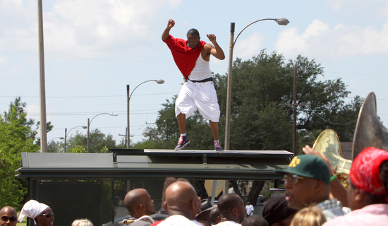 "Derrick ""Doc"" Simmons,  from the Original C.T.C. Steppers Social and Pleasure Club,  dances on top of a Carrollton Avenue bus shelter during the Original Pigeon Town Steppers second line in 2011. (Sabree Hill, UptownMessenger.com)"