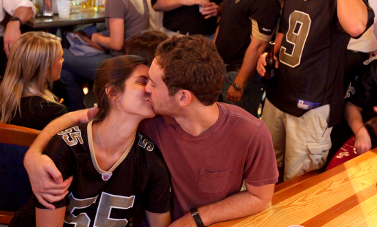 A couple kisses at a commercial break during the Saints season opener. (Sabree Hill, UptownMessenger.com)