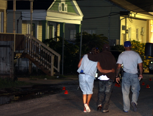 A police officer walks two grieving family members, leaning on one another for support, past the scattered shell casings to their Annunciation Street home after the slaying of Darnell Brown in April 2012. (UptownMessenger.com file photo by Robert Morris)
