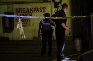 NOPD officers look for evidence at the scene of a November 2012 shooting at the corner of Annunciation and Washington, where about a dozen shell casings were marked on the ground. (UptownMessenger.com file photo by Robert Morris)