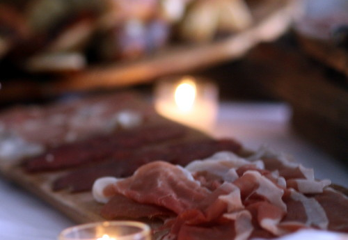 Samples of prosciutto and other cured meats await neighbors on a candlelit table. (Robert Morris, UptownMessenger.com)