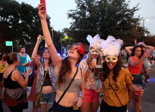 Spectators snap photos as the Krewe of OAK passes. (UptownMessenger.com)