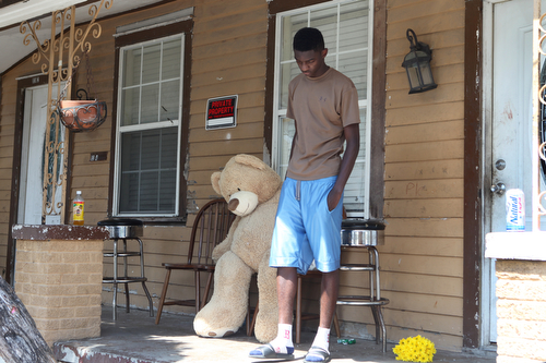 A neighbor drops off a small teddy bear at the home where an 11 year old girl was fatally shot early Monday. (Sabree Hill, UptownMessenger.com)
