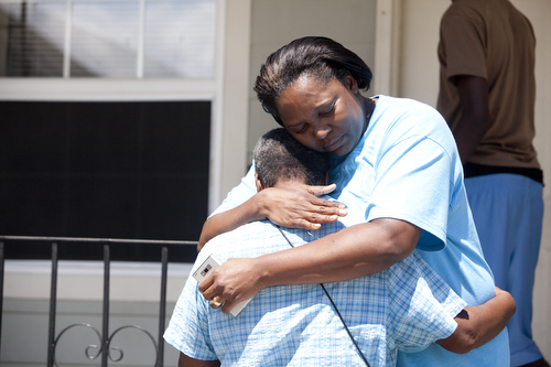 Neighbors comfort each other in the 1300 block of General Ogden St. (Sabree Hill, UptownMessenger.com)