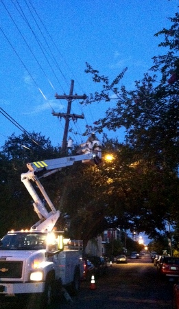 The Entergy bucket truck gamely repairs a broken power line inside a snarl of branches. (photo by Jean-Paul Villere for UptownMessenger.com)