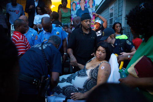 Ashley Moffet, mother of Arabian Gayles, is helped to an ambulance ambulance after fainting during the vigil.   (Sabree Hill, UptownMessenger.com)