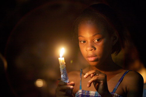 Amyri Alexander, 9, holds a candle for Arabian Gayles at the vigil. (Sabree Hill, UptownMessenger.com)