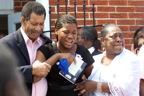 Sierra Gayles , sister of Arabian Gayles,  is supported up as she cries in pain while leaving her sisters funeral. (Sabree Hill, UptownMessenger.com)
