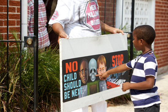 """Al Mims, who's father was shot and killed in 1987, stands outside the  funeral and shows a sign reading, """"No child should be next. Stop the killing"""".  (Sabree Hill, UptownMessenger.com)"""