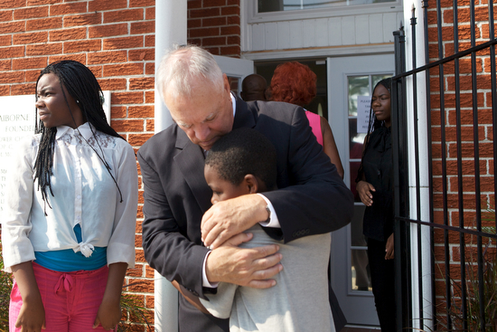 Mickey Landry, Executive Director, of Choice Foundation, gives a child a hug in front of the funeral of Arabian Gayles. Gayles went to Lafayette Academy Charter School, a Choice Foundation school. (Sabree Hill, UptownMessenger.com)