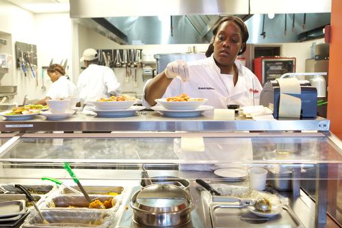 Brandi Addison prepares a pasta dish at Cafe Reconcile Thursday afternoon. (Sabree Hill, UptownMessenger.com)