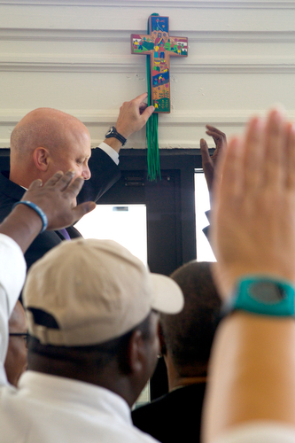 Mayor Mitch Landrieu hangs a cross over the doorway of Cafe Reconcile as guests put up their hands in prayer. (Sabree Hill, UptownMessenger.com)