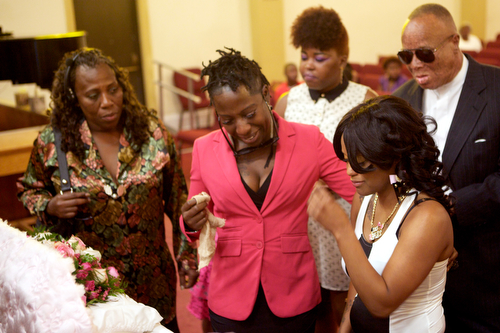 "Andrea Samuels (far right), mother of Londyn Samuels, cries as she looks at her daughter in her casket at the funeral Saturday morning. ""She was extraordinary,"" said Samuels about her daughter. (Sabree Hill, UptownMessenger.com)"
