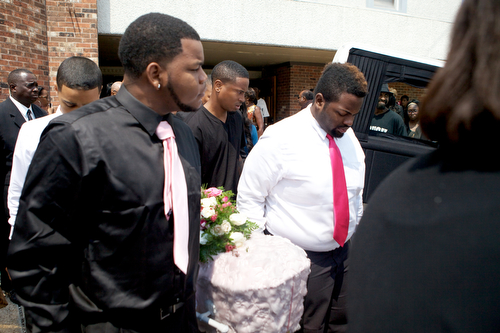 The casket  of Londyn Samuels, 1, is carried out of New Hope Baptist Church and placed in a hearse after the funeral. (Sabree Hill, UptownMessenger.com)