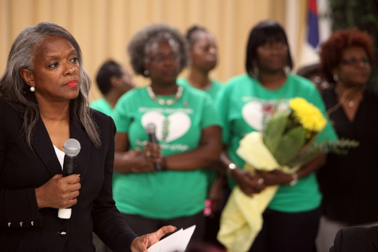 Rev. Pat Watson, executive director of Helping Mothers Heal, stands in front of a group of mothers during a ceremony Thursday evening.  (Sabree Hill, UptownMessenger.com)