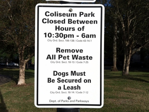 A sign at Coliseum Park reminds dog owners of laws requiring them to keep their pets leashed and pick up after them. (photo by Jean-Paul Villere for UptownMessenger.com)
