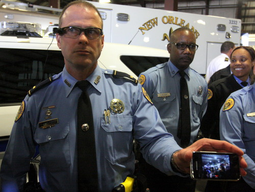 A police lieutenant demonstrates an extension of the body cameras that can be mounted on a visor or helmet. (Robert Morris, UptownMessenger.com)
