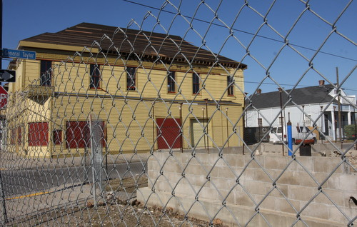 The site of the former Martin Wine Cellar on Baronne Street is still surrounded by chain-link fence, but the new roof on the old New Orleans Bicycle Club building can be seen behind it. (Robert Morris, UptownMessenger.com)