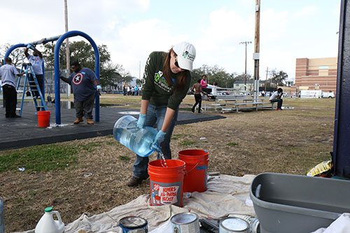 Catherine Crowell of Rebuilding Together New Orleans mixes an organic cleaner to prep a swing set for a paint job. (photo by Zach Brien for UptownMessenger.com)