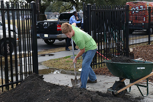 Zach George, a member of Parkway Partners, shovels dirt for the brand-new gardens at Carter G. Woodson school. The gardens will be integrated into the school's curriculum. (photo by Zach Brien for UptownMessenger.com)