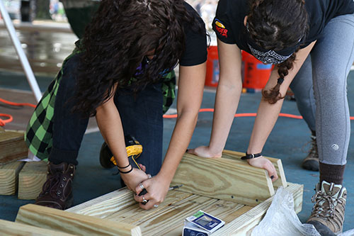 Lauren Capriglionel, left, and Mariel Quintana, right, build benches around the basketball court. Capriglionel and Quintana are from Rutgers University in New Jersey. They came to New Orleans just to volunteer. (photo by Zach Brien for UptownMessenger.com)