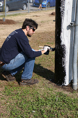 Jon Skvarka, director of Rebuilding Together, repaints a light post at A.L. Davis Park. (photo by Zach Brien for UptownMessenger.com)