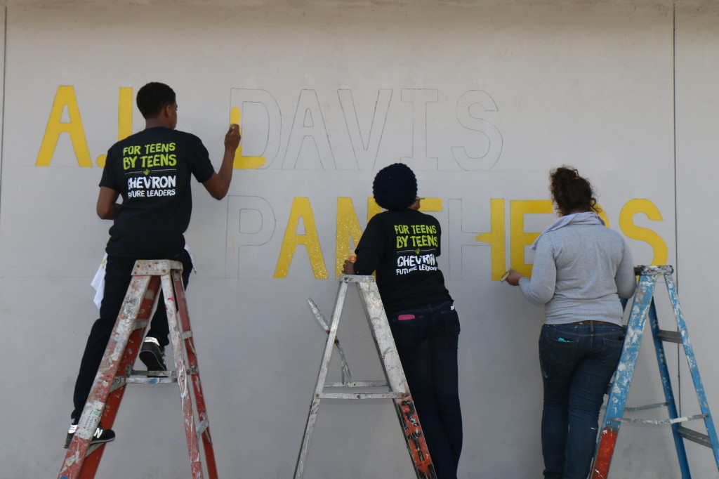 "Tyler Johns, left, Shanay Haywood, center, and Rachel May, right, paint ""A.L. Davis Panthers"" on the outside of A.L. Davis park. (photo by Zach Brien for UptownMessenger.com)"