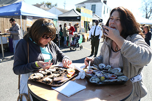 Helen Valenti (left) and Dori Ehlinger (right) enjoy some raw oysters at the first annual Freret Street Oyster Jam. (Zach Brien, UptownMessenger.com)
