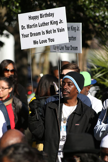 Onlookers hold up commemorative signs in honor of Martin Luther King Jr.