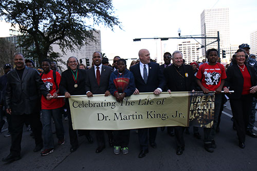 U.S. Attorney Kenneth Polite (middle left), Mayor Mitch Landrieu (middle right), Archbishop Gregory Aymond (far right) and others lead the 27th annual MLK Jr. Day parade down Poydras Ave.