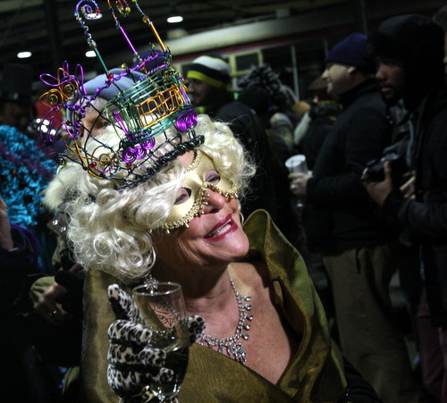 "Wearing a streetcar tiara, a member of the Phunny Phorty Phellows wishes everyone a ""Happy Mardi Gras"" before boarding the St. Charles Avenue streetcar on Monday evening. (Robert Morris, UptownMessenger.com)"
