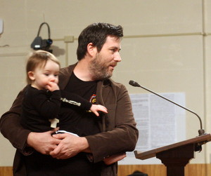 Scott Wood, co-owner of the Courtyard Brewery, speaks to the City Planning Commission on Tuesday with 18-month-old Jules in his arms.