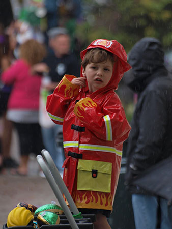 Aspiring firefighter puts aside his ambitions to catch some beads. Krewe of Carrolton 2014. (Zach Brien, UptownMessenger.com)
