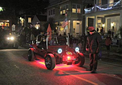 A man peers at a miniature lit-up car during the Krewe of Ancient Druids (Della Hasselle, MidCityMessenger.com).