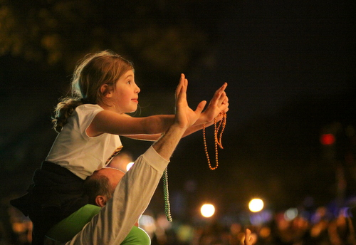 A child waits expectantly for throws from the Krewe of Oshun. (Robert Morris, UptownMessenger.com)