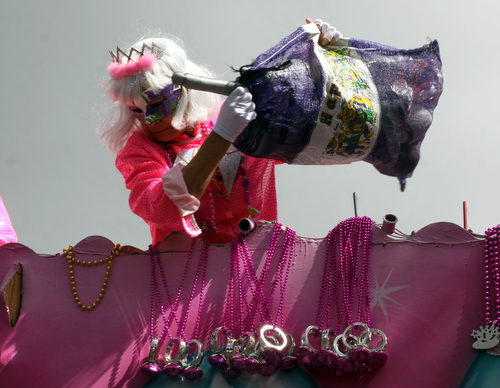 "A rider on the Iris ""Diamond"" float pulls out a new bag of throws. (Robert Morris, UptownMessenger.com)"