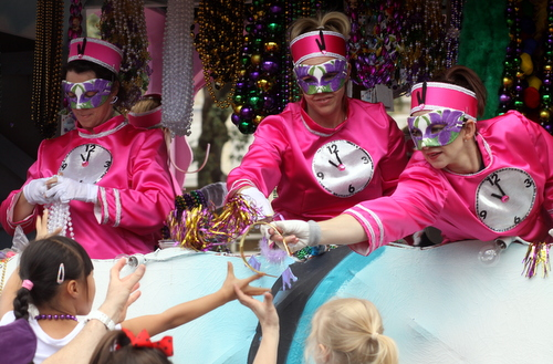 Riders in the Krewe of Iris hand throws to the crowd. (Robert Morris, UptownMessenger.com)
