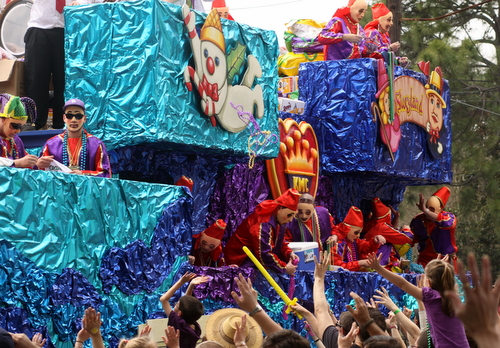 """The Krewe of Mid-City """"Tribute to City Park"""" float rolls down Magazine, as smoke from the train on the front wafts over the crowd. (Robert Morris, UptownMessenger.com)"""