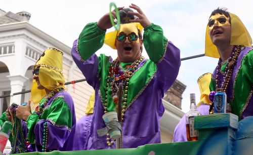 A rider in the Krewe of Okeanos holds a throw over the crowd. (Robert Morris, UptownMessenger.com)