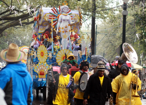 "The Free Agents Brass Band rhythm section keeps time through the rain ahead of the Rex ""Ishtar"" float. (Robert Morris, UptownMessenger.com)"