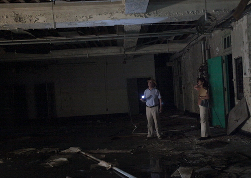 John Wettermark and Barbara Griffin stand near water pooling in the first floor of the Priestley building. (Robert Morris, UptownMessenger.com)