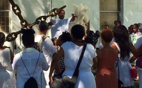 A participant in the Maafa ceremony speaks at the Tomb of the Unknown Slave. (photo by jewel bush for UptownMessenger.com)