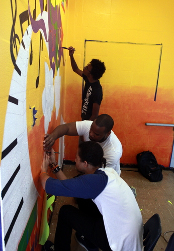 Volunteers paint a mural in a third-floor stairwell at the former Benjamin Banneker campus. (Robert Morris, UptownMessenger.com)