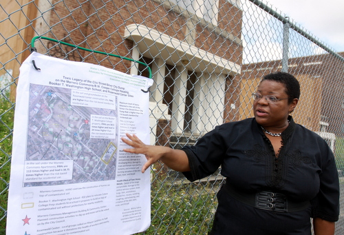 Attorney Monique Harden points to areas of contaminated soil around a map of the Booker T. Washington site on the fence in front of the school. (Robert Morris, UptownMessenger.com)