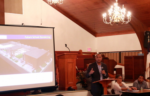 RSD Superintendent Patrick Dobard presents a rendering of the Booker T. Washington school during a meeting Tuesday night at Pure Light Baptist Church. (Robert Morris, UptownMessenger.com)