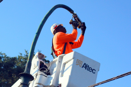 Anthony Reed installs a new LED light on a St. Charles Avenue streetlight pole. (Robert Morris, UptownMessenger.com)