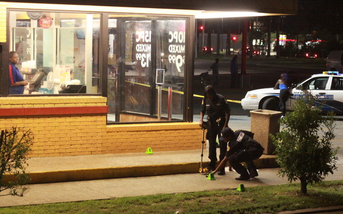 New Orleans police investigate a shooting Sunday night in front of the Church's Chicken restaurant in the 1500 block of South Claiborne. (Robert Morris, UptownMessenger.com)