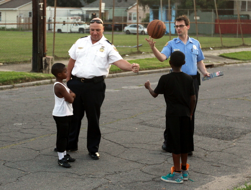 Commander Ronnie Stevens trades a fist bump with a child on Dryades Street while Detective Drew Deacon spins a basketball on Wednesday, Sept. 24. (Robert Morris, UptownMessenger.com)